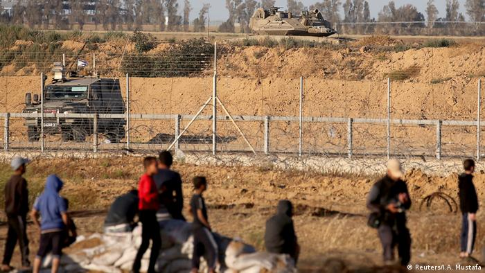 Protesters stand in front of Israeli military vehicles at the separation wall between Gaza and Israel