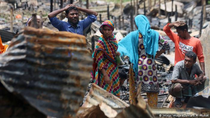 Several people stand amid destroyed dwellings