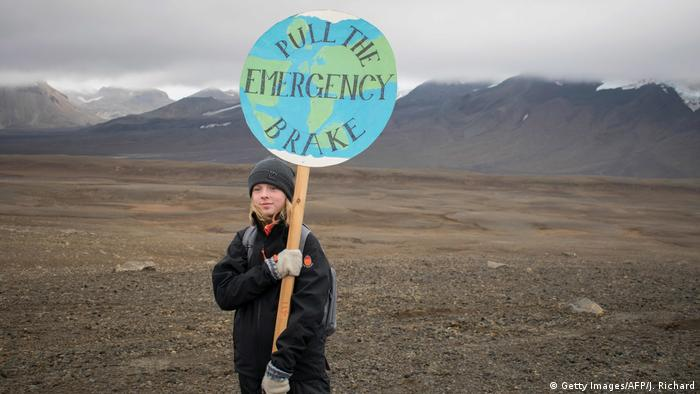 A girl attending the ceremony to mark the passing of Iceland's Okjokull ice sheet holds a globe-shaped placard with a picture of the earth and the slogan pull the emergency brake.