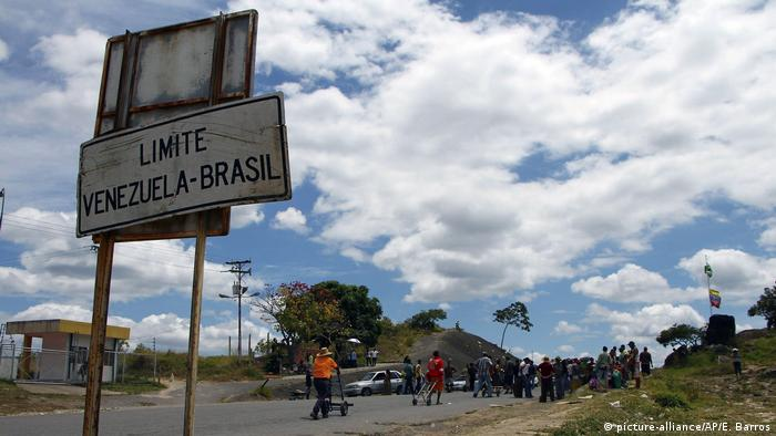 Venezuelans await the opening of the border crossing at Pacaraima, Brazil