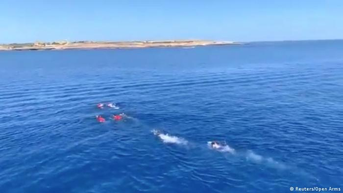 A still image taken from a video shows migrants attempting to swim ashore after jumping off the Spanish rescue ship Open Arms.