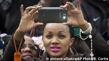 A Kenyan Catholic woman takes photographs with her smartphone as she awaits the arrival of Pope Francis to hold a Mass at the campus of the University of Nairobi in Kenya Thursday, Nov. 26, 2015. The Argentine pope, who has never been to Africa before, was treated to ululating Swahili singers, swaying nuns, Maasai tribesmen and traditional dancers at the Mass on the grounds of the University of Nairobi. (AP Photo/Ben Curtis) |