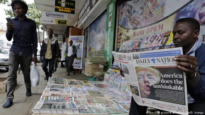 A man reads the daily nation newspaper at a newsstand in Nairobi