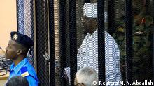 Sudan's former president Omar Hassan al-Bashir stands guarded inside a cage at the courthouse where he is facing corruption charges, in Khartoum, Sudan August 19, 2019. REUTERS/Mohamed Nureldin Abdallah