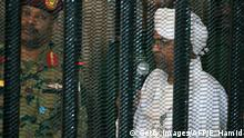 19.08.2019 Sudan's deposed military ruler Omar al-Bashir stands in a defendant's cage during the opening of his corruption trial in Khartoum on August 19, 2019. - Bashir has admitted to receiving $90 million in cash from Saudi monarchs, an investigator told a Khartoum court today. (Photo by Ebrahim HAMID / AFP) (Photo credit should read EBRAHIM HAMID/AFP/Getty Images)