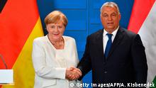 19.08.2019 German Chancellor Angela Merkel and Hungarian Prime Minister Viktor Orban shake hands following a press conference during their meeting in the Hungarian-Austrian border town of Sopron on August 19, 2019, to mark the 30th anniversary of the Pan European Picnic. - During the Pan-European Picnic in August 1989 at the Hungarian-Austrian border, at least 600 East Germans crossed the border and escaped to freedom in the West, which became a pivotal moment in the fall of the Iron Curtain. (Photo by Attila KISBENEDEK / AFP) (Photo credit should read ATTILA KISBENEDEK/AFP/Getty Images)