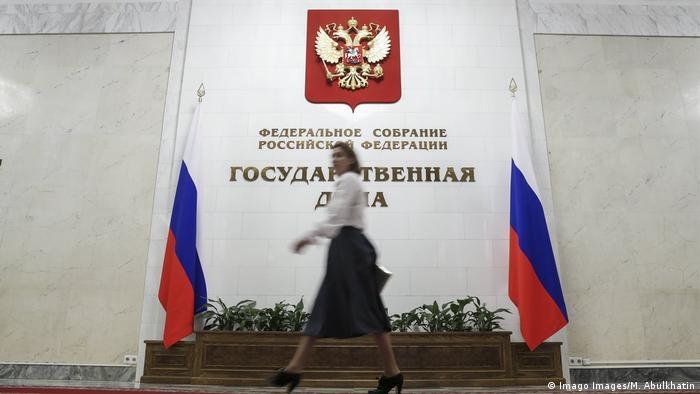 Девушка проходит мимо флагов России и барельефа на стене - герба России и надписи Государственная дума
