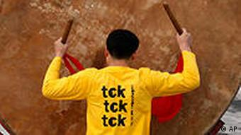 Chinese drummers wearing T-shirts bearing slogans Save the climate, no time to waste and tck tck tck in Beijing