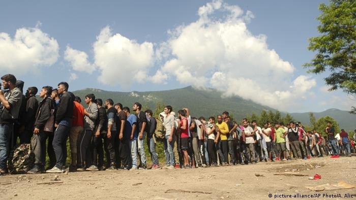 Migrants and refugees wait in line to receive supplies from the Red Cross at the Vucijak camp outside Bihac, Bosnia.