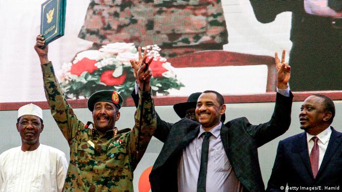 Sudan's military council chief and protest leader raise their hands celebrating the signing of the constitutional declaration paving the way for civilian rule