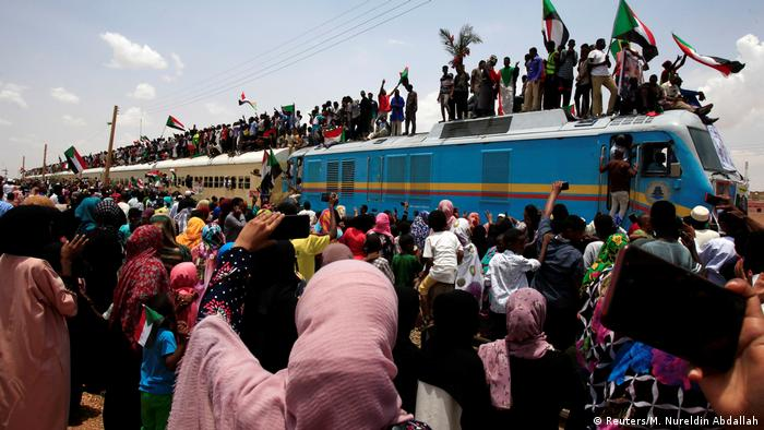 Sudanese civilians celebrating in front of and atop a train over the signing of a power sharing deal