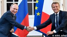 French President Emmanuel Macron, right, shakes hands with Russian President Vladimir Putin after their meeting at the fort of Bregancon in Bormes-les-Mimosas, southern France, Monday Aug. 19, 2019. French President Emmanuel Macron and Russian President Vladimir Putin are meeting to discuss the world's major crises, including Ukraine, Iran and Syria, and try to improve Moscow's relations with the European Union. (Gerard Julien, Pool via AP)