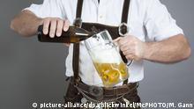junger Mann in bayerischer Lederhose fuellt eine Mass Bier, Deutschland, Bayern | traditional bavarian man drinking mass beer, Germany, Bavaria | Verwendung weltweit