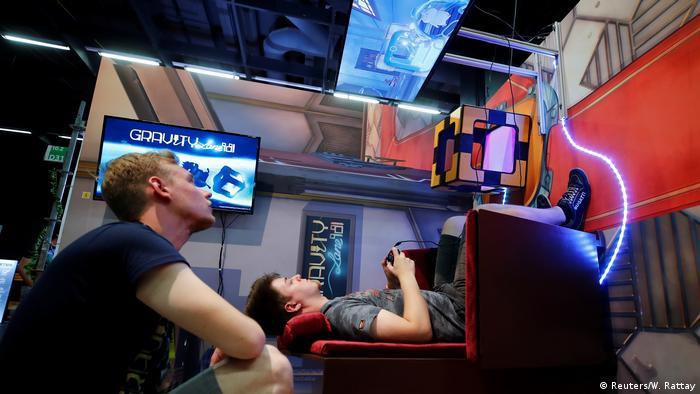 Gamers view a ceiling monitor (Reuters/W. Rattay)