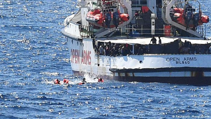 Several migrants swim away from the Open Arms, a Spanish rescue ship