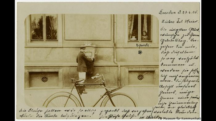 postcard from 1905 showing a postboy delivering mail to a post box with his delivery bike (Museum für Kommunikation Berlin)