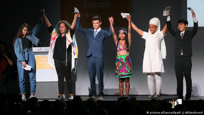 Young speakers hold up their hands on stage at the Religions for Peace 10th World Assembly (picture-alliance/dpa/K.-J. Hildenbrand)