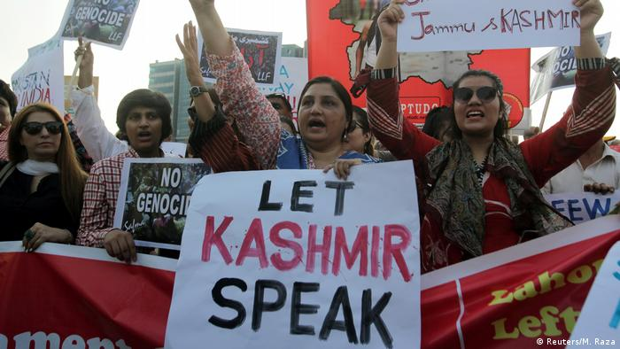 People carry signs as they chant slogans to express solidarity with the people of Kashmir, during a rally in Lahore, Pakistan.
