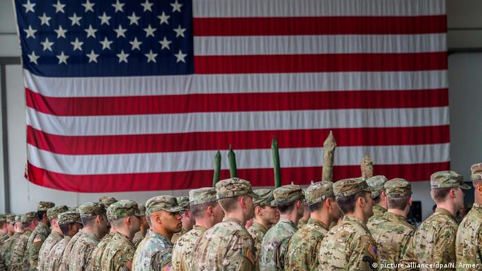 Rows of US soldier standing in front of a huge American flag (picture-alliance/dpa/N. Armer)