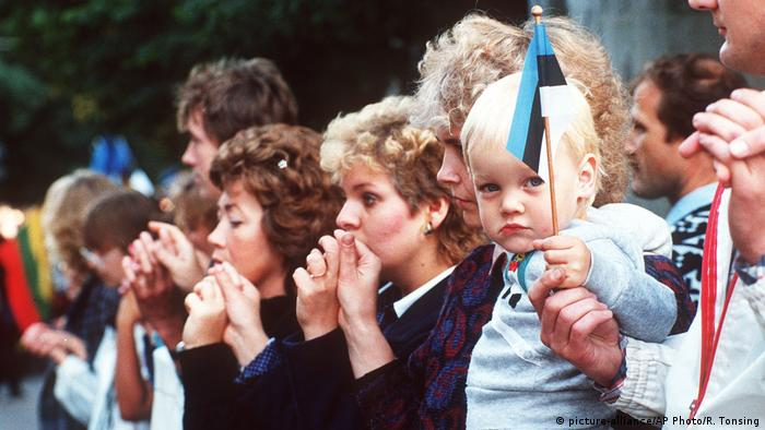Residents of Tallin join hands in 1989 to form a human chain in solidarity, including a toddler hodling an Estonian flag (picture-alliance/AP Photo/R. Tonsing)