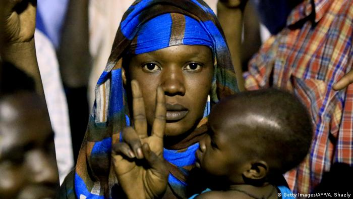 A Sudanese woman carrying a baby and making the v-sign for victory. (Getty Images/AFP/A. Shazly)