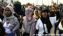 Sudanese women and men celebrate outside the Friendship Hall in the capital Khartoum where generals and protest leaders signed a historic transitional constitution meant to pave the way for civilian rule in Sudan, on August 17, 2019. - The constitutional declaration formalises the creation of a transition administration that will be guided by an 11-member sovereign council, comprised of six civilians and five military figures. The agreement brought an end to nearly eight months of upheaval that saw masses mobilise against president Omar al-Bashir, who was ousted in April after 30 years in power. (Photo by Ebrahim HAMID / AFP) (Photo credit should read EBRAHIM HAMID/AFP/Getty Images)