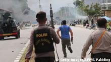 21.08.2019 Indonesian policemen disperse protesters in Timika, Indonesia's restive Papua province, on August 21, 2019. - Indonesia's Papua was hit by fresh unrest on August 21 as more than 1,000 security personnel were sent to the restive region after violent protests that saw buildings torched and street battles between police and demonstrators. (Photo by SEVIANTO PAKIDING / AFP) (Photo credit should read SEVIANTO PAKIDING/AFP/Getty Images)