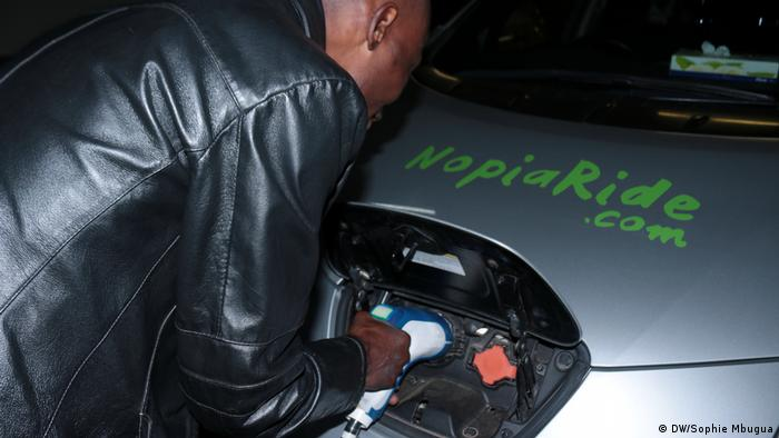 A taxi driver charges his electric car