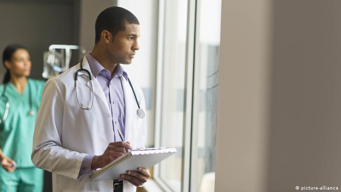 A doctor looks out a window at a hospital