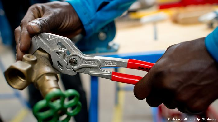 A photo of the hands of a refugee working on plumbing