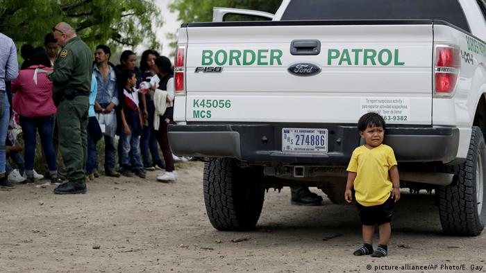 A kid crying in front of a US Border Patrol truck with families in the background (picture-alliance/AP Photo/E. Gay)