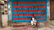 TOPSHOT - This photo taken on August 16, 2019 shows a man sitting next to graffiti that reads We Want Freedom on a shuttered store in the Soura locality in Srinagar, during a lockdown imposed by Indian authorities after stripping Kashmir of its autonomy. - In an act of defiance against New Delhi's controversial decision to strip the Muslim-majority region of its autonomy, Soura neighbourhood on the outskirts of Kashmir's main city of Srinagar has sealed itself off from security forces. (Photo by Jalees ANDRABI / AFP) / TO GO WITH: India-unrest-Kashmir-Pakistan, FOCUS by Jalees Andrabi (Photo credit should read JALEES ANDRABI/AFP/Getty Images)