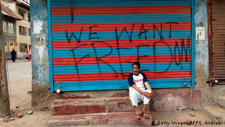 A man sits in front of a closed shop in Srinagar