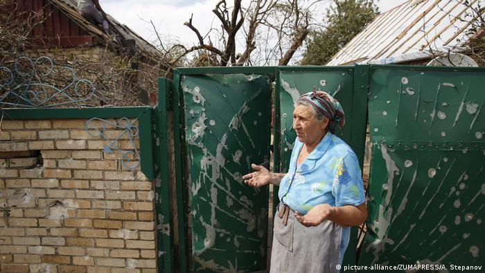 Ukraine Sajzewe   Ältere Frau reagiert vor Ihrem durch Artilleriebeschuss zerstörten Haus (picture-alliance/ZUMAPRESS/A. Stepanov)