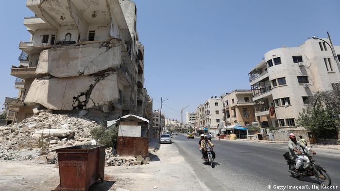 Motorbikes riding past ruined building in Idlib. (Getty Images/O. Haj Kadour)