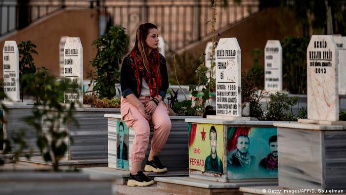 Девушка на могиле родственника в Сирии