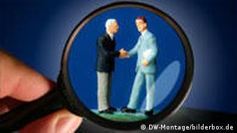 Symbolbild Handschlag Geschäftsmänner unter der Lupe