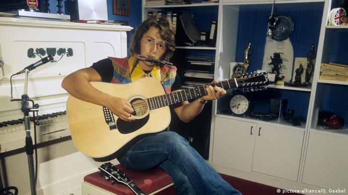 Peter Maffay sitzt auf einem Klavierschemel und spielt Gitarre (picture-alliance/G. Goebel)