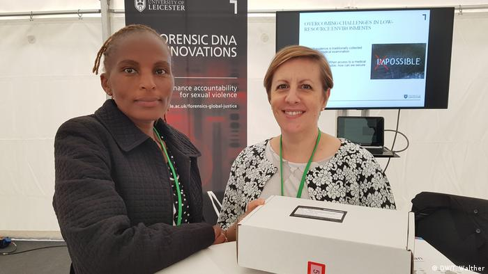 Wangu Kanja and Lisa Smith hold up their rape kit box at the Religions for Peace assembly in Germany