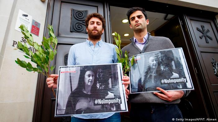 The Caruana Galizia brothers hold pictures of their mother which read #NoImpunity