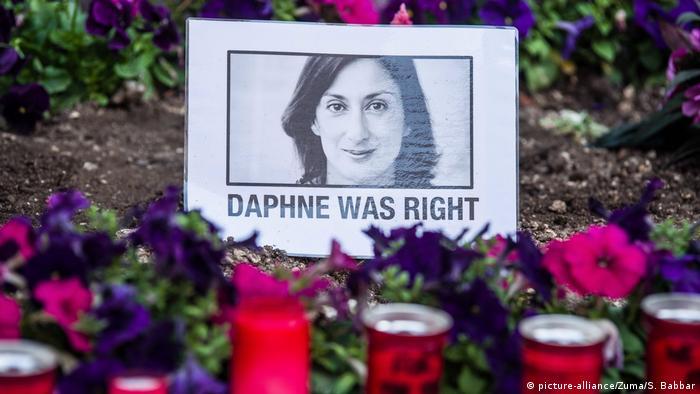 Fotografia da jornalista Daphne Caruana Galizia, morta em 2017, rodeada por flores e velas
