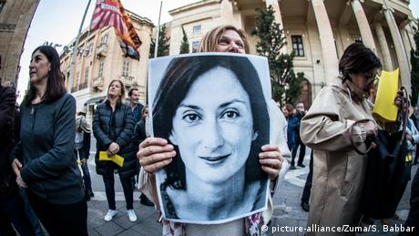 A protestor holds a photo of murdered journalist Daphne Caruana Galizia during a vigil demanding justice