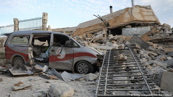 Искореженный микроавтобус и разрушенная больница в Идлибе