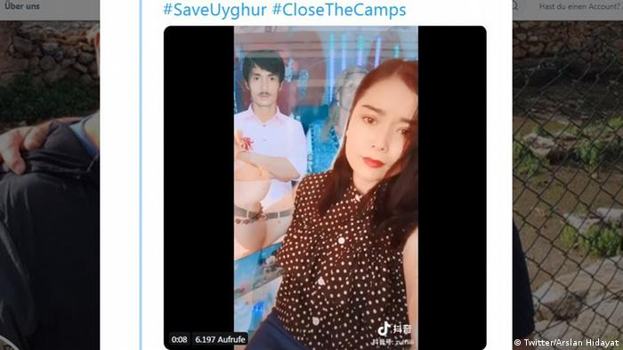 A screenshot of a Tweet featuring a crying Uyghur woman holding a picture of a man and woman.