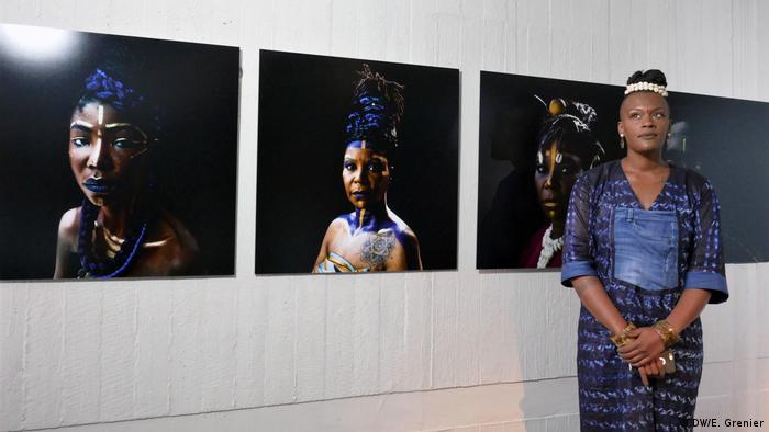 Die Künstlerin und Kuratorin Ken Aïcha Sy steht vor ihrer Fotoserie im Kunstgewerbemuseum | Connecting Afro Futures (DW/E. Grenier)
