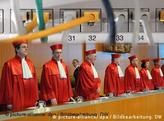 Seven constitutional court judges in red robes in front of a computer