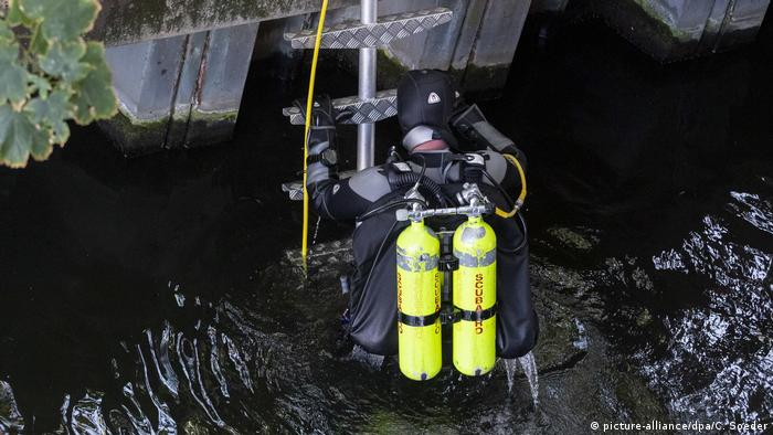 A police diver retrieves evidence thrown in the Spree River following a killing in Berlin, Germany