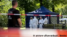 Criminal investigators secure the scene where a 40-year-old man was fatally shot at a park in Berlin, Germany