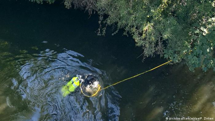 A police diver searches the Spree River looking for evidence from a fatal shooting at a park in Berlin, Germany