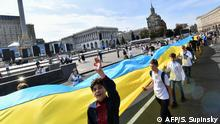People carry a huge flag as they take part in a march marking the Day of the National Flag of Ukraine in the centre of Kiev on August 23, 2019. (Photo by Sergei SUPINSKY / AFP)